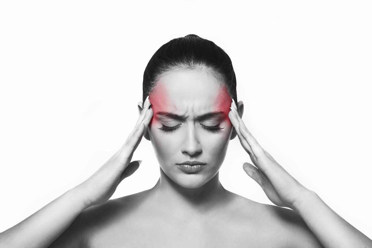 Woman in pain with headache holding her head