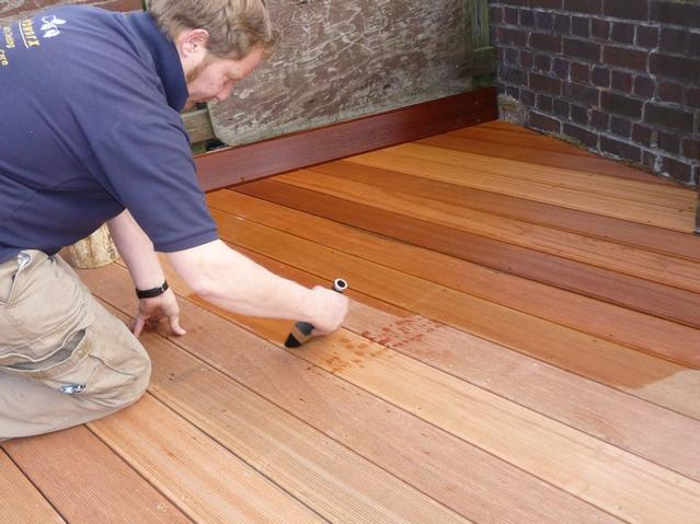 Wood floor sealing services: oiling decking using 12 inch brush towards grain of the wood.