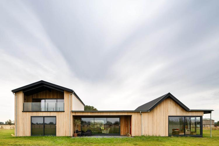 Gally's Farm – A modern, new build farm house This timber-framed bungalow with an adjacent barn was built with its environment very much in mind. Drawing inspiration from the buildings that pepper its South Cambs countryside surroundings, Gally's Farm was vertically clad in long strips of larch. Sliding barn doors were custom built and designed by Inti Construction for the barn end of the building and then were mirrored elsewhere on the house.