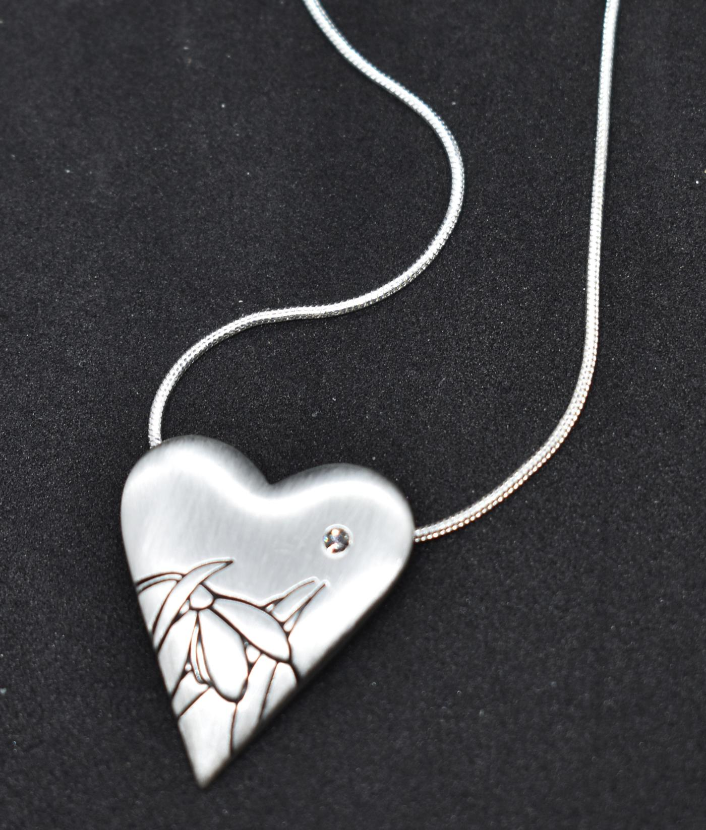 Fashion Necklace: Silver Necklace with a single cubic zirconia encrusted heart